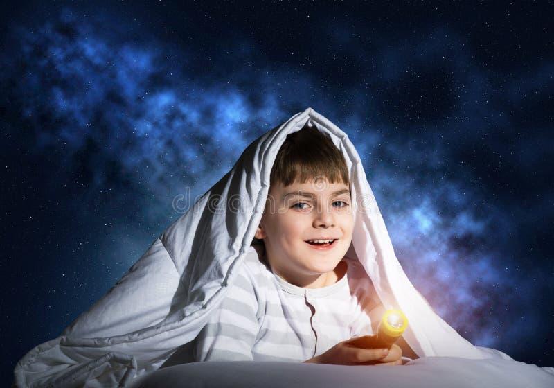 Glückliches Kind mit der Taschenlampe, die unter Decke sich versteckt lizenzfreies stockfoto
