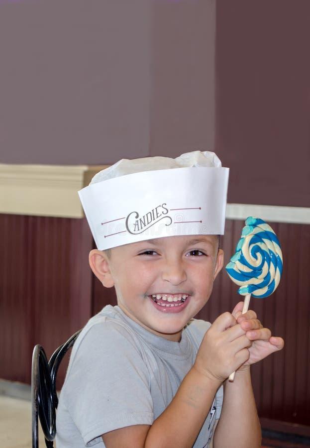 Glückliches Kind mit großem Lutschbonbonknall stockfotografie
