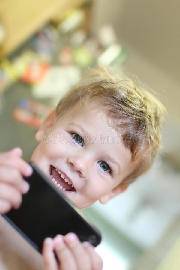 Glückliches Kind mit Handy stockfotografie