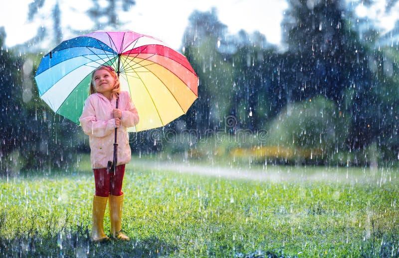 Glückliches Kind mit Regenbogen-Regenschirm stockfotografie