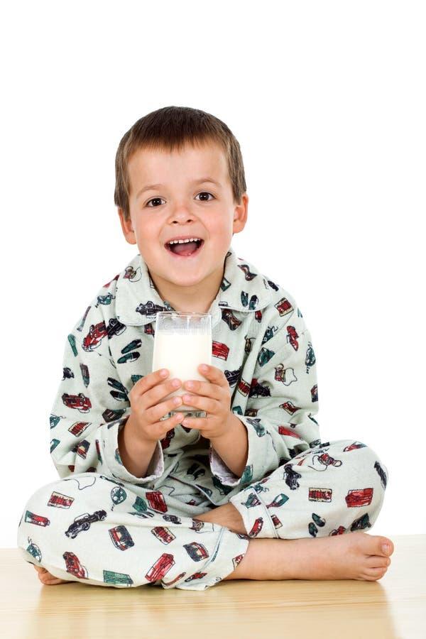 Glückliches Kind mit seinem Schlafenszeitglas Milch lizenzfreies stockfoto