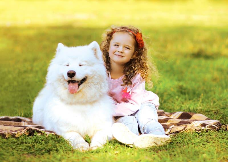 Glückliches Kind und Hund, die auf dem Gras stillsteht lizenzfreie stockfotos