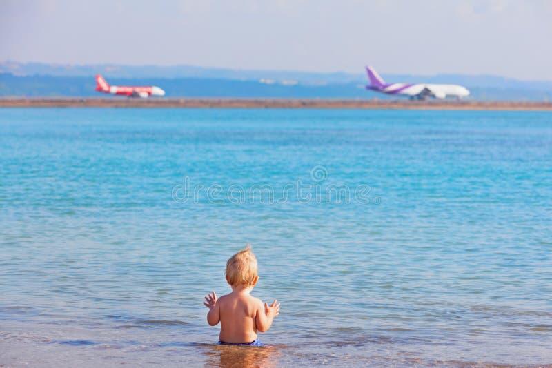 Glückliches Kinderaufpassende Flugzeuglandung am Strandflughafen lizenzfreie stockfotografie