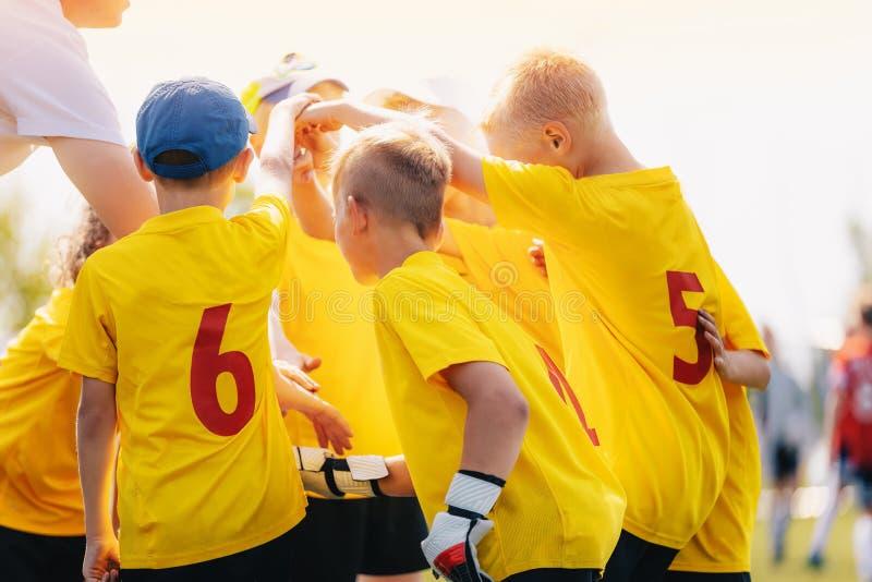 Glückliches Kinderfußballteam, das zusammen Hand vor Spiel die Köpfe zusammensteckt und stapelt lizenzfreies stockfoto