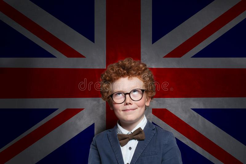 Glückliches Kinderjungenenglisch studen oben schauen auf dem BRITISCHEN Flaggenhintergrund Lernen Sie englisches Konzept stockbild