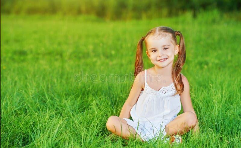 Glückliches Kinderkleines Mädchen im weißen Kleid, das auf Gras Sommer liegt lizenzfreie stockfotos