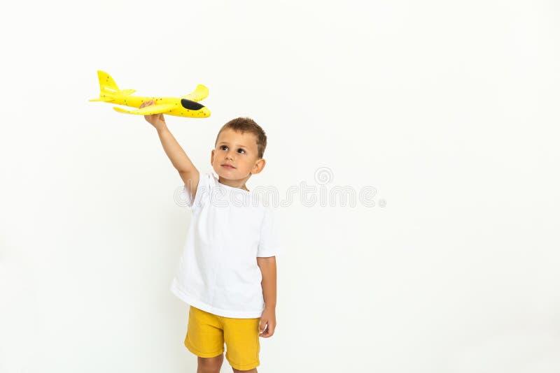 Glückliches Kinderkleinkind, das mit gelbem Spielzeugflugzeug spielt lizenzfreies stockfoto