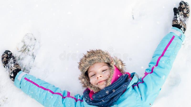 Glückliches Kindermädchen, das auf einem gefrorenen klaren Schnee niederlegt lizenzfreies stockfoto