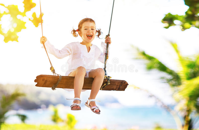 Glückliches Kindermädchen, das auf Schwingen am Strand im Sommer schwingt stockbild
