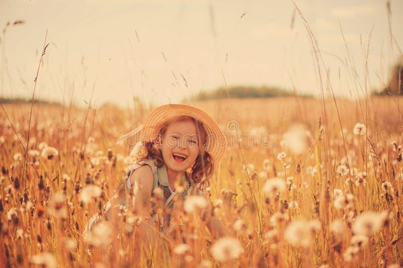 Glückliches Kindermädchen, das auf Sommerwiese mit dangelions geht Ländliche Landhausstilszene, Tätigkeiten im Freien lizenzfreie stockbilder