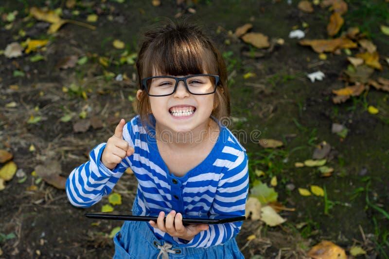 Glückliches Kindermädchen, das in camera mit glücklichem und ruhigem Ausdruck in den Gläsern, halten in seiner Handpc-Tablette sc stockfotos
