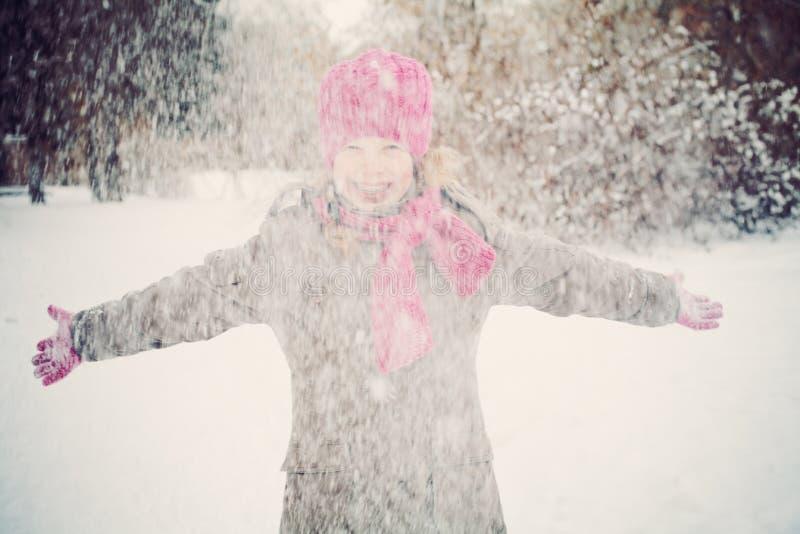 Glückliches Kindermädchen, das den Spaß spielt mit Schnee hat lizenzfreie stockbilder