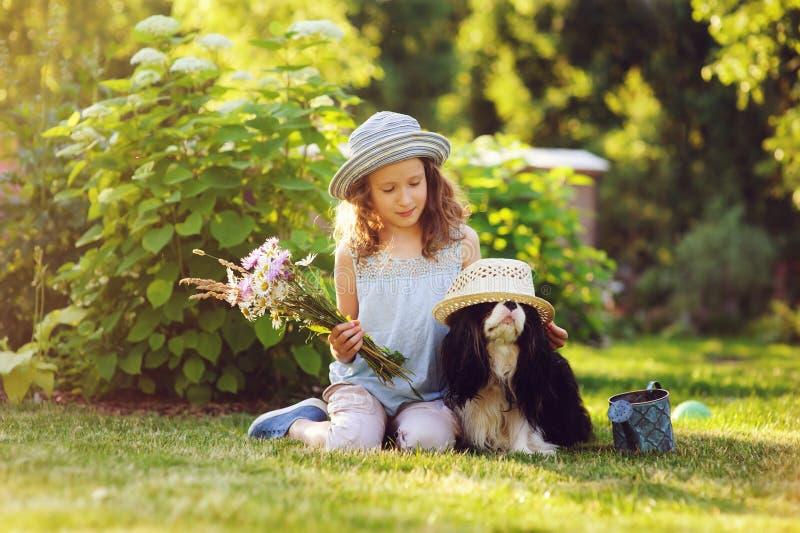 Glückliches Kindermädchen, das im Sommergarten mit ihrem Spanielhund sich entspannt stockbilder