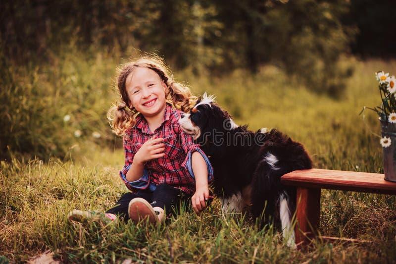 Glückliches Kindermädchen, das mit ihrem Hund am Sommertag spielt stockfotografie