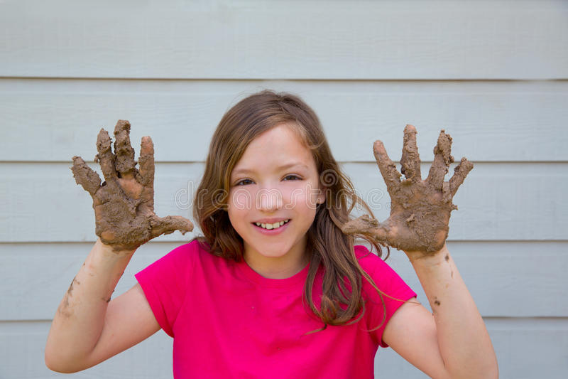 Glückliches Kindermädchen, das mit Schlamm mit dem schmutzigen Handlächeln spielt stockfotografie