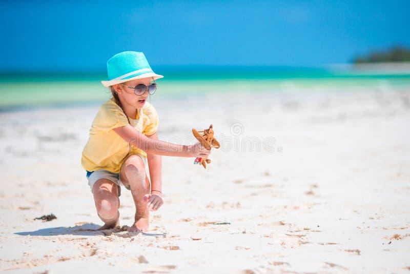 Glückliches Kindermädchen, das mit Spielzeugflugzeug auf dem Strand spielt Scherzt Traum des Werdens ein Pilot lizenzfreie stockbilder