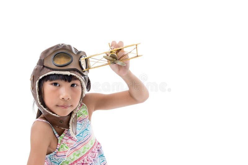 Glückliches Kindermädchen, das mit Spielzeugflugzeug spielt stockbild