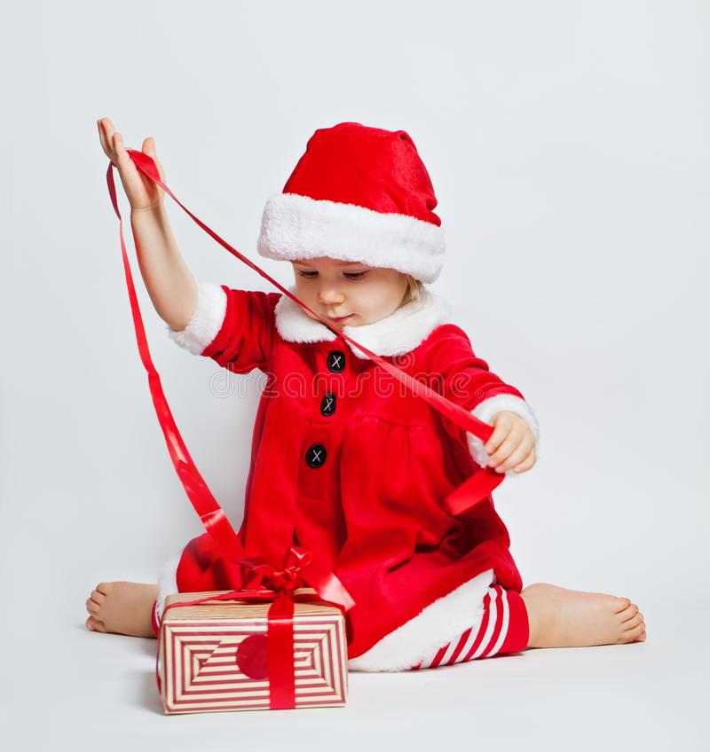 Glückliches Kindermädchen, das Sankt-Hut öffnende Weihnachtsgeschenkbox trägt stockfoto