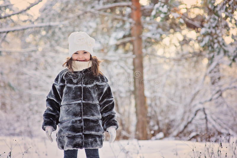 Glückliches Kindermädchen, das Spaß im schneebedeckten Wald des Winters hat lizenzfreie stockbilder