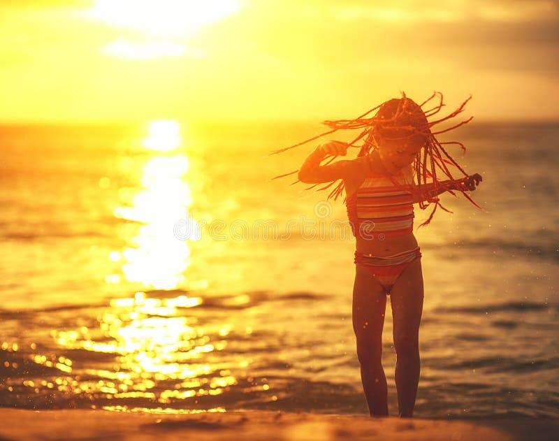 Glückliches Kindermädchen im Badeanzug mit Fliegenhaartanzen auf Strand bei Sonnenuntergang stockfotos