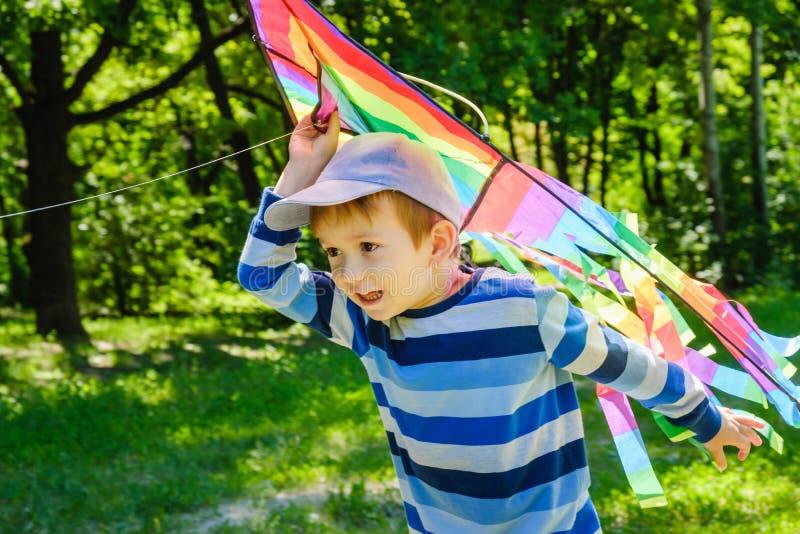 Glückliches Kindermädchen mit einem Drachen, der auf Wiese im Sommer in der Natur läuft lizenzfreie stockfotografie