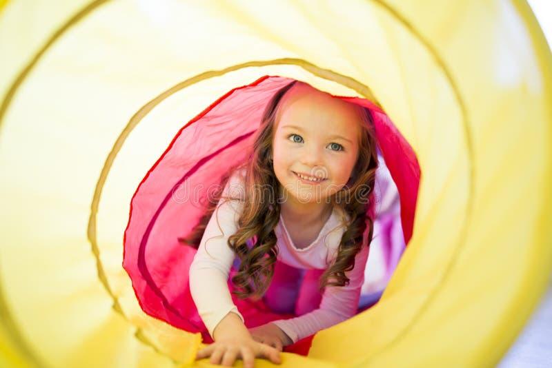 Glückliches Kindermädchen spielt Innen in einem Tunnel stockbild