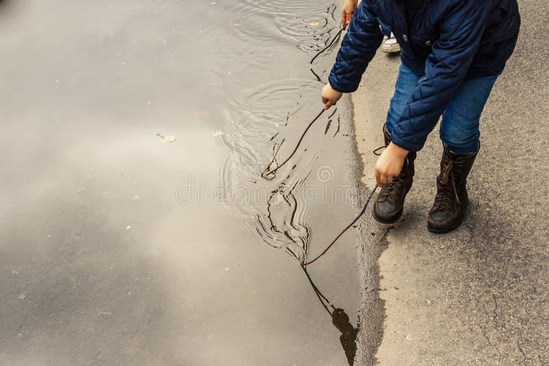 Glückliches Kindermädchen und braune Lederstiefel in der Pfütze auf einem Herbst gehen Kleinkindmädchen nach Regen läuft nahe den stockbild