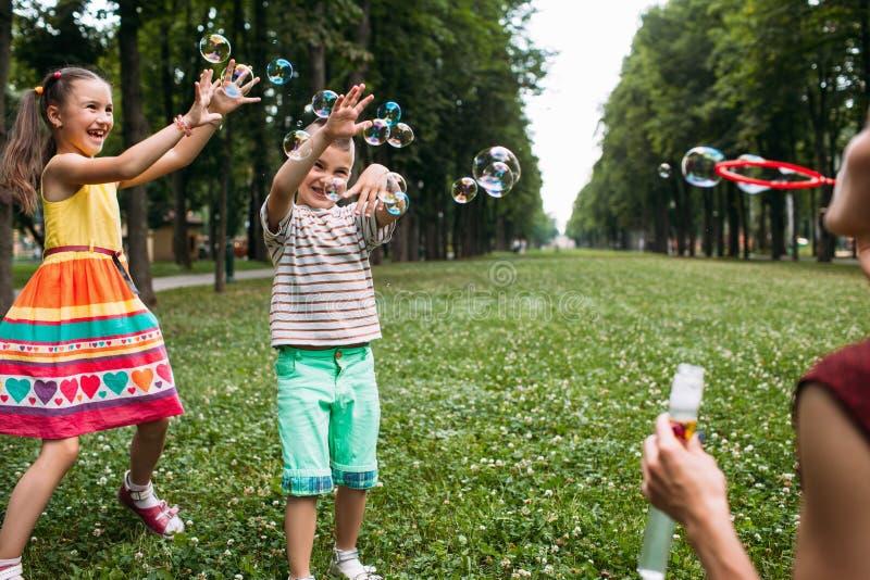 Glückliches Kinderschlagblasen-Parkkonzept stockbild