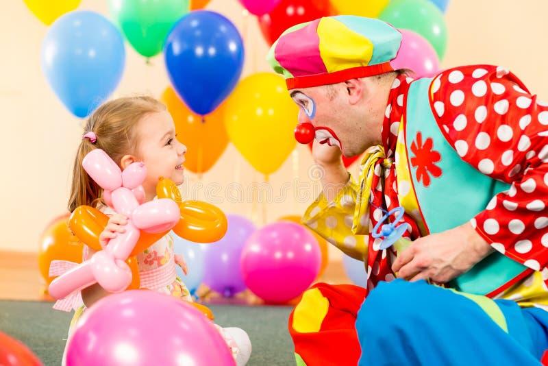 Glückliches Kindmädchen, das mit Clown auf Geburtstag spielt stockbilder