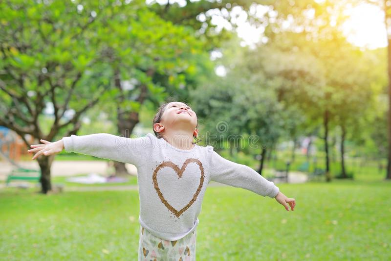 Glückliches kleines asiatisches Kindermädchen öffnete ihre Hände und oben schauen im frischen Sommergarten stockbild