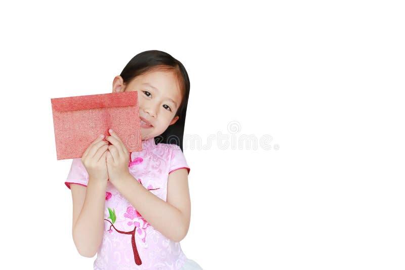 Glückliches kleines asiatisches Kindermädchen, das rosa traditionelles lächelndes cheongsam Kleid beim Empfangen des roten Umschl stockfotos