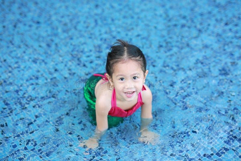 Glückliches kleines asiatisches Kindermädchen in einem Meerjungfrauklage Lügenpoolside mit dem Schauen der Kamera stockbilder
