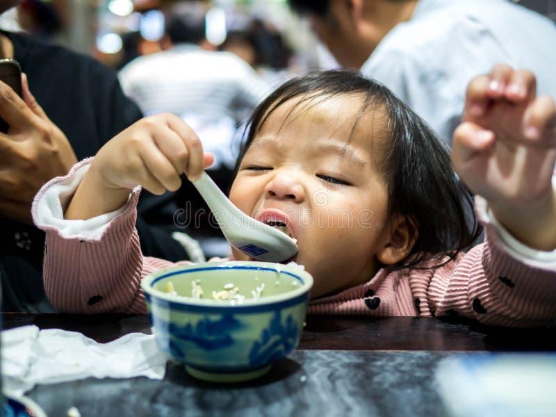 Glückliches kleines asiatisches Mädchen, das Reis durch selbst am Restaurant, Familienkonzept isst lizenzfreies stockbild