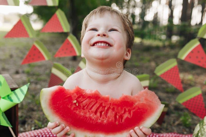 Glückliches kleines Baby, welches die Wassermelone im Freien isst lizenzfreie stockfotografie