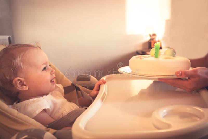 Glückliches kleines Kind, das Geburtstagskuchen mit brennender Kerze in seinem ersten alles Gute zum Geburtstag betrachtet stockbild