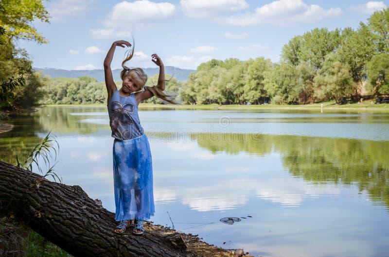 Glückliches kleines Kind, das Haltungen im Baumstamm durch das Fluss benk macht lizenzfreies stockfoto
