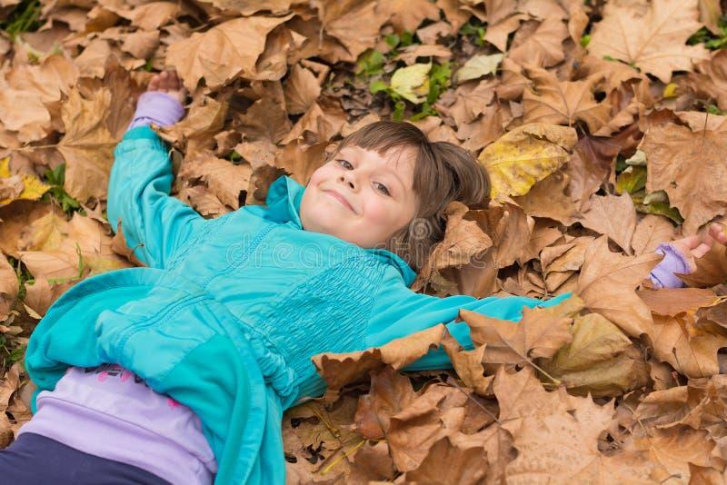 Glückliches kleines Kind, das im Herbst lacht und spielt lizenzfreie stockfotografie