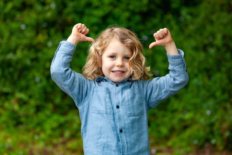 Glückliches kleines Kind mit dem langen blonden Haar und O.K. sagen lizenzfreie stockfotos