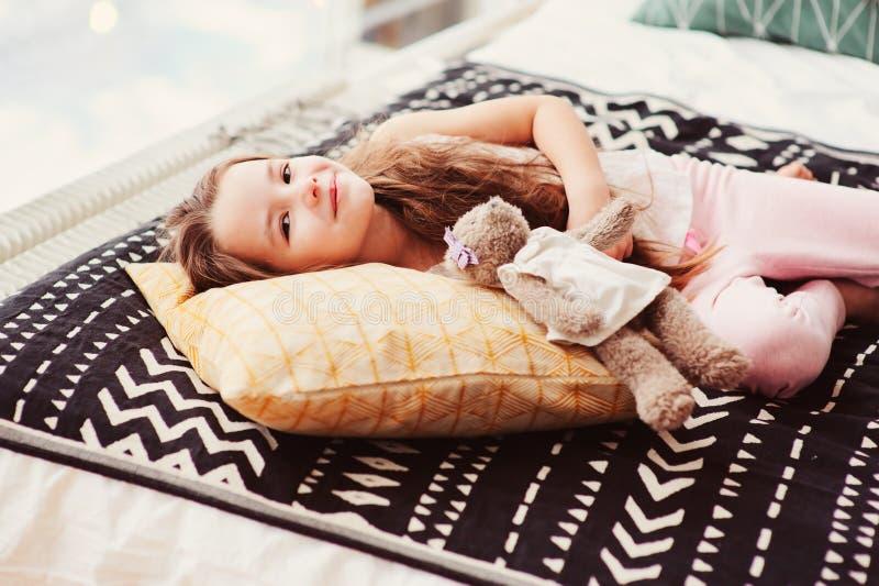 glückliches kleines Kindermädchen, das morgens auf ihrem Bett, wachend im bequemen Raum liegt auf stockfoto