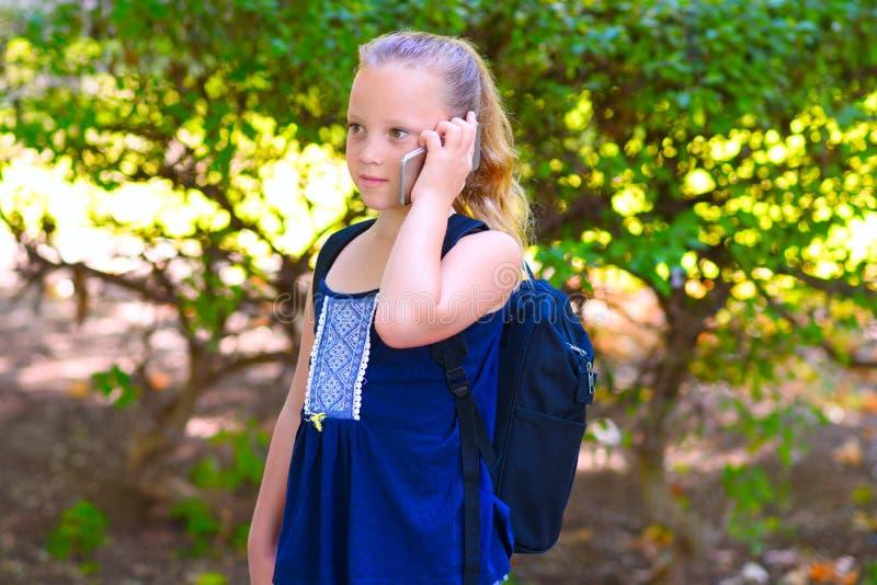 Glückliches kleines Kindermädchen gehen zu schulen und sprechend am Handy am Stadtpark stockbilder