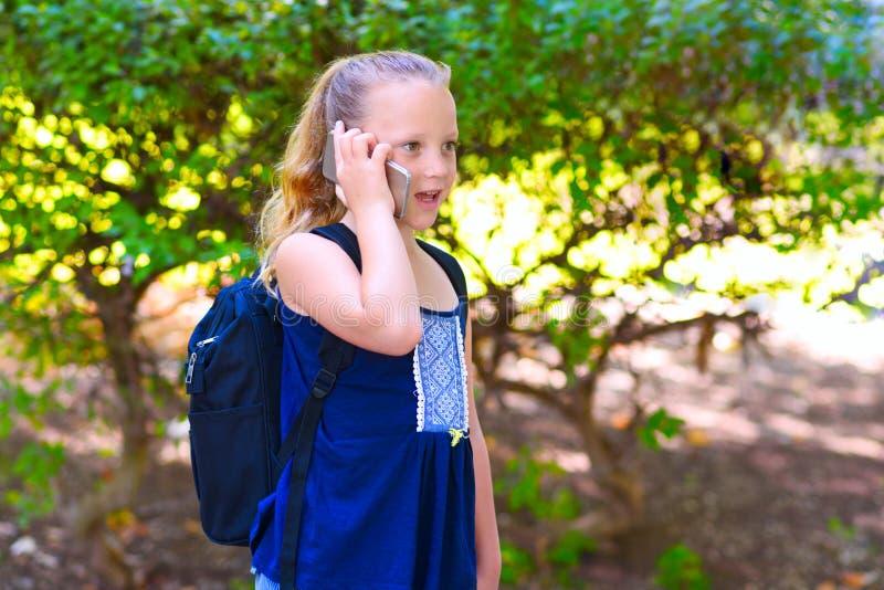 Glückliches kleines Kindermädchen gehen zu schulen und sprechend am Handy am Stadtpark stockfoto