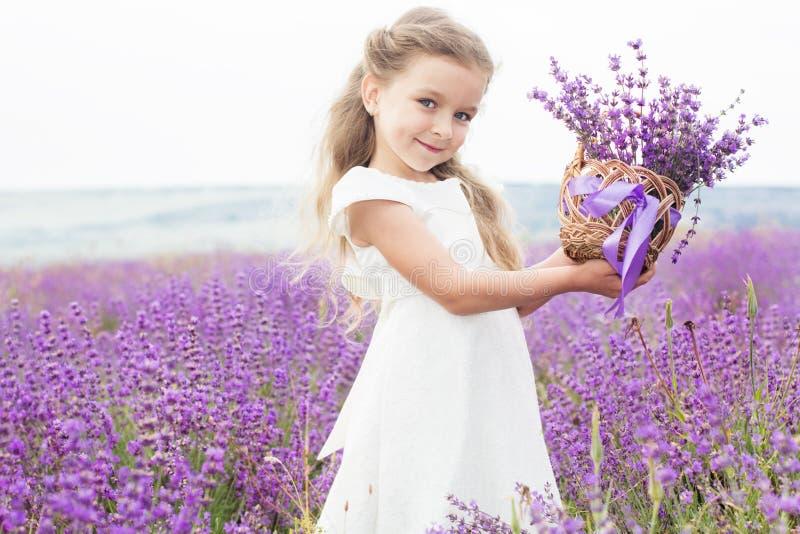 Glückliches kleines Mädchen auf dem Lavendelgebiet mit Korb von lizenzfreie stockfotos