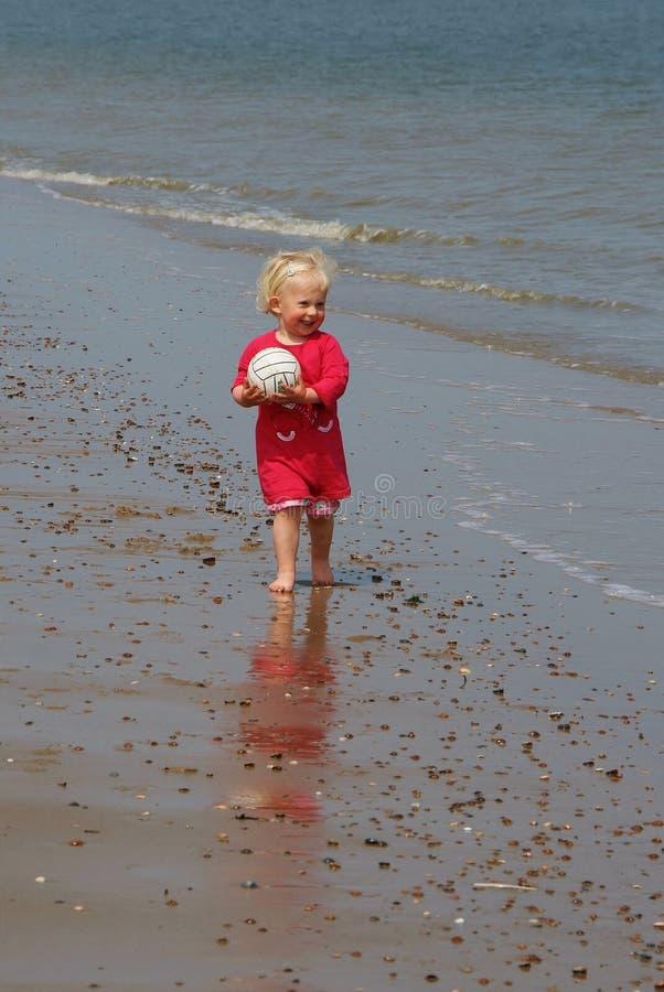 Glückliches kleines Mädchen auf dem Strand mit einem Ball stockbild