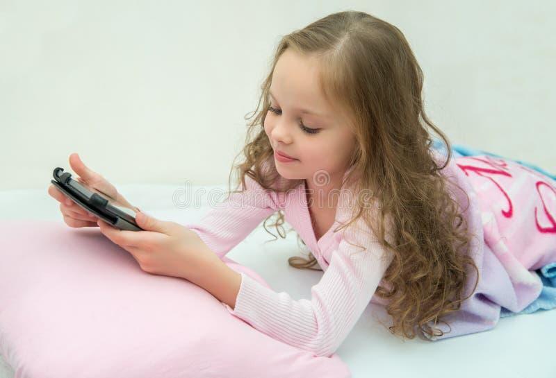 Glückliches kleines Mädchen, das auf Bett mit Tablet-Computer liegt stockfotos