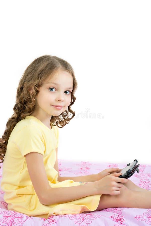 Glückliches kleines Mädchen, das auf Bett mit Tablet-Computer liegt stockfoto