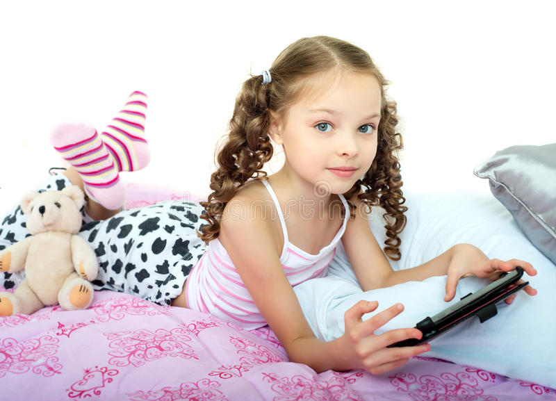 Glückliches kleines Mädchen, das auf Bett mit Tablet-Computer liegt stockbild