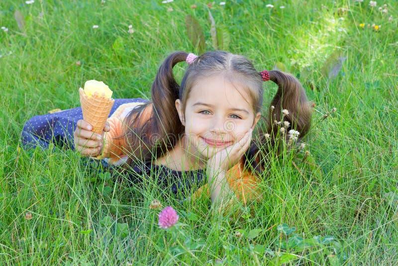 Glückliches kleines Mädchen, das auf dem Gras mit Eiscreme in ihrer Hand liegt stockfotos