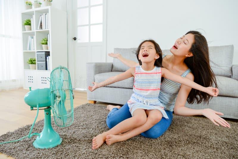Glückliches kleines Mädchen, das auf jungen Mutterbeinen sitzt stockbild