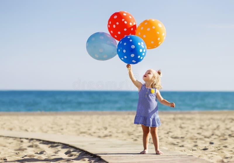 Glückliches kleines Mädchen, das Bündel bunte Luftballone an hält lizenzfreie stockbilder