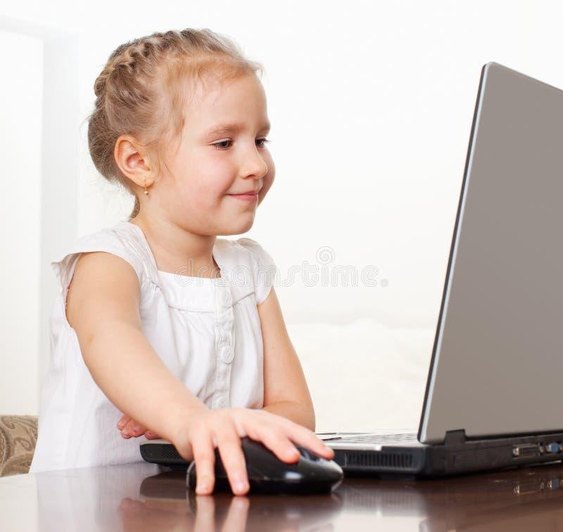 Glückliches kleines Mädchen, das Computer spielt stockbilder